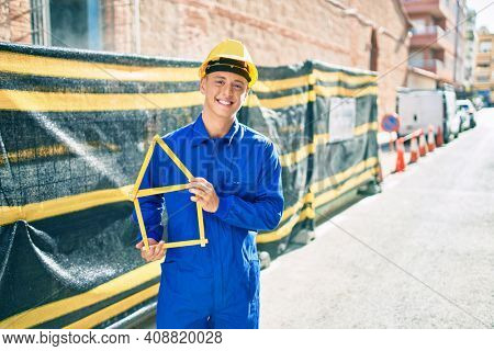 Young hispanic workman smiling happy holding build project at street of city