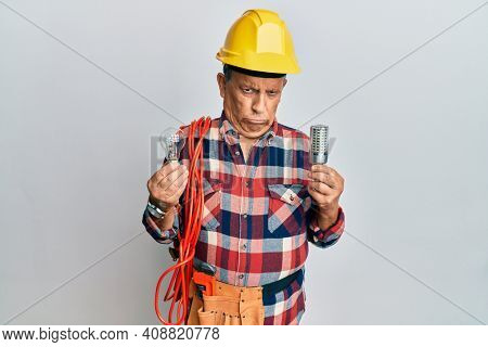 Senior hispanic man wearing handyman uniform holding led lightbulb and incandescent bulb skeptic and nervous, frowning upset because of problem. negative person.