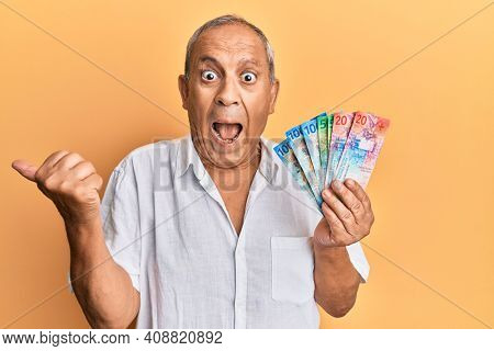 Handsome mature senior man holding swiss franc banknotes pointing thumb up to the side smiling happy with open mouth