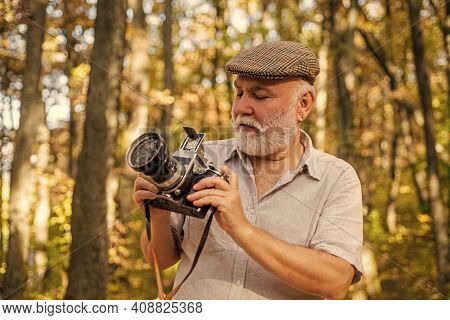 Photo Session Using Natural Light. Senior Man Take Photo On Autumn Day. Old Photographer Hold Photo