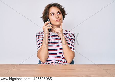 Young hispanic woman talking on the smartphone sitting on the table serious face thinking about question with hand on chin, thoughtful about confusing idea