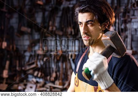 Authentic Blacksmith Man Forges A Metal Product In Dark Indoors Studio