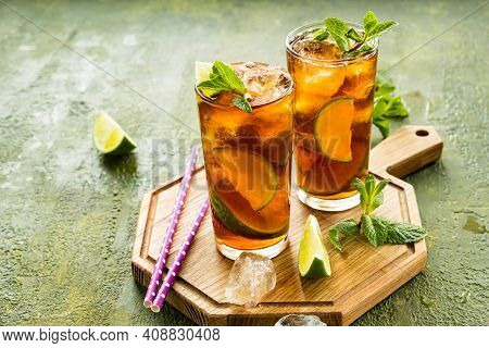 Refreshing Drink, Iced Tea With Lime Wedges In Glasses On A Wooden Board On A Green Concrete Backgro