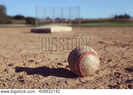 Baseball laying in the dirt by the pitcher's mound