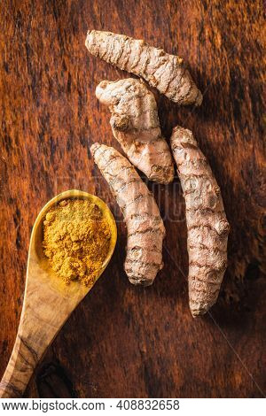 Indian turmeric powder and root. Turmeric spice. Ground turmeric in wooden spoon on wooden table.