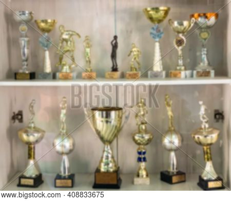 Cupboard With Sports Cups Won At Sports Competitions. Blurred Pictures Through Glass