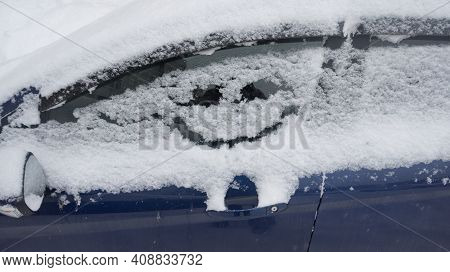 The Car Is Covered With Snow. A Smiley Face Is Drawn On The Car Window. Smile, Humor. Good Mood Conc