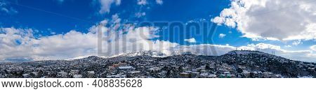 Attica Greece. Penteli Mountain Covered With Snow, Aerial Drone View, Blue Cloudy Sky Background