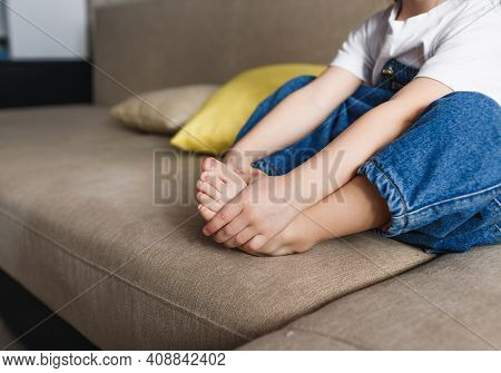 A Little Girl In A Blue Denim Jumpsuit Is Sitting On The Couch With Her Arms Wrapped Around Her Legs