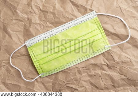 Green Surgical Protective Medical Everyday Mask Against Bacteria. Crumpled Wrinkled Kraft Paper Back