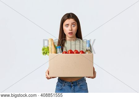 Online Home Delivery, Internet Orders And Grocery Shopping Concept. Confused Woman Holding Box With