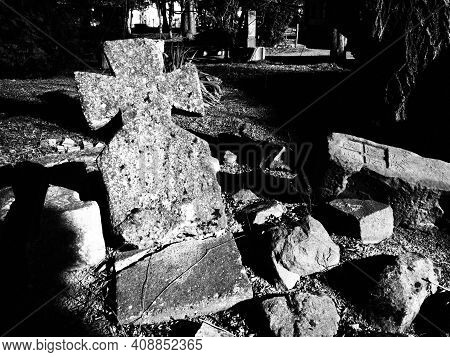 Cross. Headstone At A Catholic Christian Cemetery. A Lopsided Stone Monument. Unknown Grave In The R
