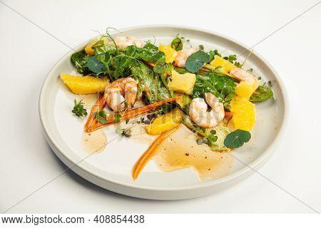 Shrimp Salad In Soy-ginger Dressing On A Plate. Ingredients Iceberg Lettuce, Shrimp, Spinach, Orange