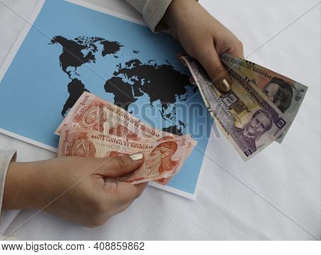 Hands Of A Woman Holding Honduran Money And A World Map On The Table