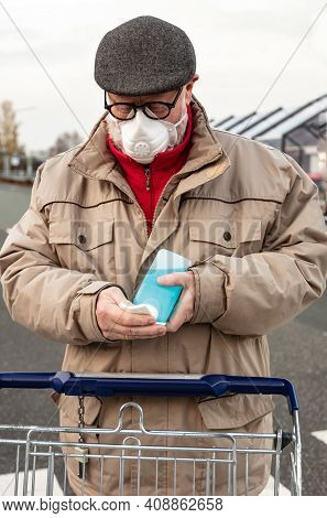 Man With Disinfectant In A Plastic Bottle And A Shopping Cart