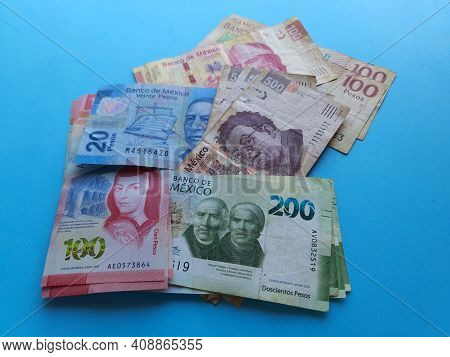 Stacked Mexican Banknotes Of Different Denominations On The Blue Background