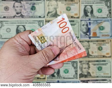 Hand Holding Norwegian Banknote Of 100 Kroner And Background With American Dollar Bills