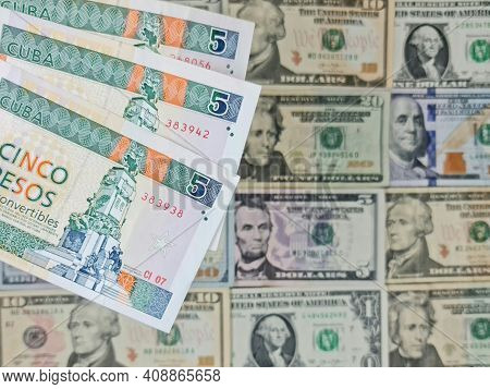 Approach To Cuban Banknotes Of Five Pesos And Background With American Dollar Bills