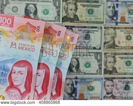 Approach To Mexican Banknotes Of 100 Pesos And Background With American Dollar Bills