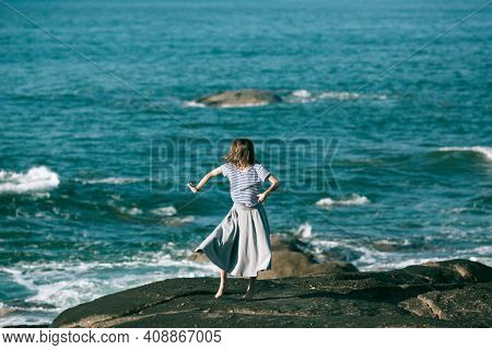 Dancer woman is engaged in choreography on the rocky Alantic coast.