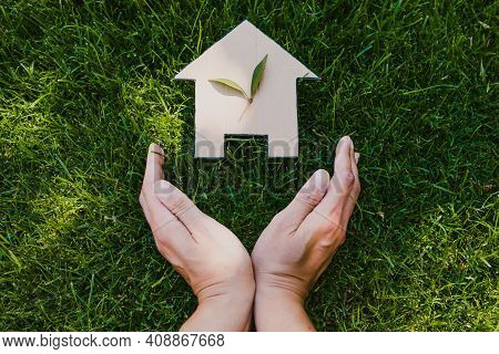 Green Home And Eco-friendly Construction Conceptual Image, House Icon On Green Grass Lawn Under The
