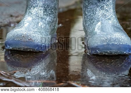 The Sparkly Blue Rainboots Of A Lttle Girl Standing In A Puddle After A Rain Shower.