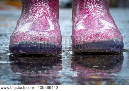 The Sparkly Pink Rainboots Of A Lttle Girl Standing In A Puddle After A Rain Shower.