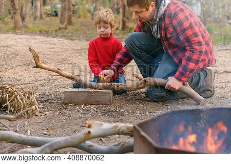Father Helping His Son To Cut A Log With Wood Saw For A Camping Fire, Kuitpo Forest, South Australia