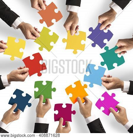 Bunch Of Hands Holding The Puzzle Game Pieces,and Trying To Complete The Puzzle