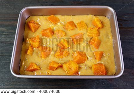 Butternut Squash Cake Batter In A Cake Pan Topped With Diced Squashes Ready For Baking