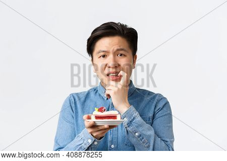 Close-up Of Tensed And Worried Asian Guy Tempting To Eat Piece Of Cake While On Diet, Biting Finger