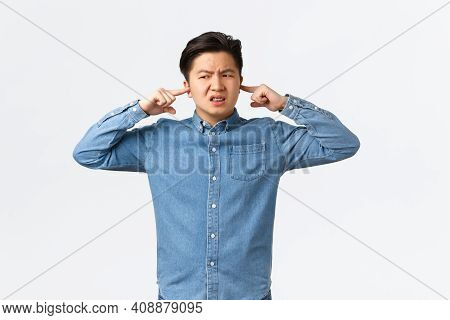 Disturbed And Frustrated Asian Man Complaining Loud Noise, Shut Ears And Looking Left Displeased, Fr