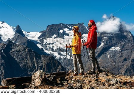 Trekking And Nordic Walking. Young Couple Doing Nordic Walking In The Mountains. Active Rest On The