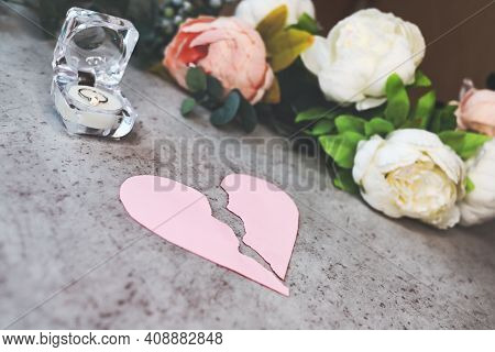 Torn Pink Heart On Table Next To Box Of Wedding Rings And Flowers. Concept Of Divorce, Separation, I
