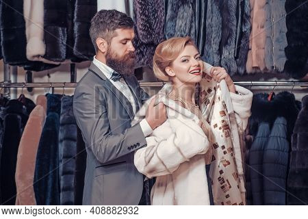 Fashion And Beauty, Fur. Couple Of Man And Woman In Fur Coat. Shopping, Seller And Customer. Luxury