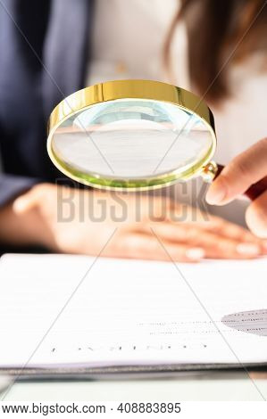 Auditor Hand Document Investigation With Magnifying Glass
