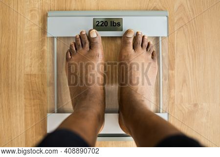 Obesity And Weightloss. Feet On Weight Scale. Pounds