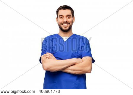 healthcare, profession and medicine concept - happy smiling doctor or male nurse in blue uniform with crossed arms over white background
