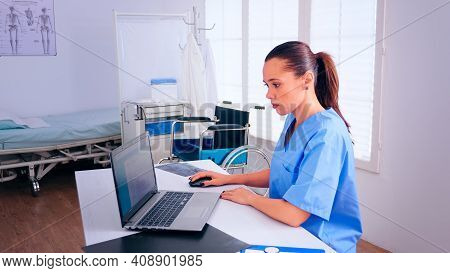 Nurse Analysing List Of Patients On Laptop, Therapist Typing On Computer Consult Patient Online. Med