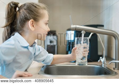 Little Girl Open A Water Tap With Her Hand Holding A Transparent Glass. Kitchen Faucet. Filling Cup