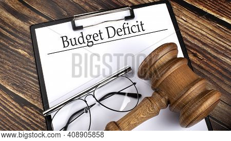 Paper With Budget Deficit With Gavel, Pen And Glasses On Wooden Background