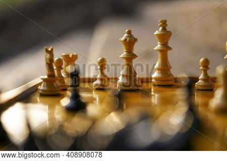 Chess Board With White Figures On A Sunny Day With Bokeh And Blurred Black Figures And Background
