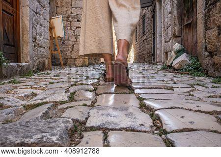 Detail Shot Of Female Legs Wearing Comfortable Travel Sandals Walking On Old Medieval Cobblestones S