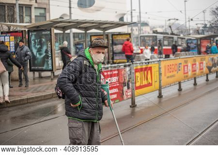 Brno, Czech Republic. 02-17-2021. Old Man With Walking Stick Crossing The Tram Rails With Face Mask