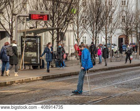 Brno, Czech Republic. 02-17-2021. Handicap Man Crossing Tram Rails With Walking Sticks With Face Mas