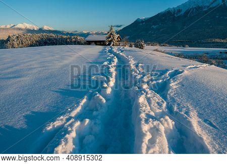 Deep Snow Trail Path In Sunlit Alpine Winter Landscape During Sunset In Wildermieming, Tirol, Austri