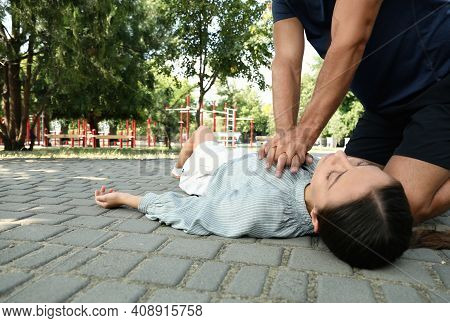 Man Performing Cpr On Unconscious Young Woman Outdoors. First Aid
