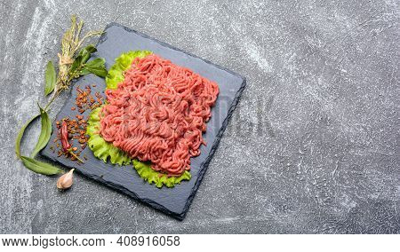 Fresh Minced Pork And Beef, Garnished With Garlic, Red Pepper And Dill On A Slate Stone.dark Texture