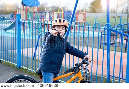 Kid Poiting Finger Out, School Kid Learns To Ride A Bike In The Park, Portrait Of Little Boy On Bicy