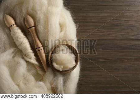 Soft White Wool And Spindles On Wooden Table, Flat Lay. Space For Text